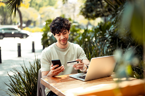 Young man sitting at the cafe and paying online with credit card