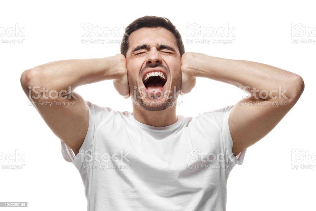 Hombre joven gritar en ruidosos vecinos arriba, destaca por el increíble ruido, cerrando los oídos con ambas manos, evitar escuchar gran pelea - foto de stock