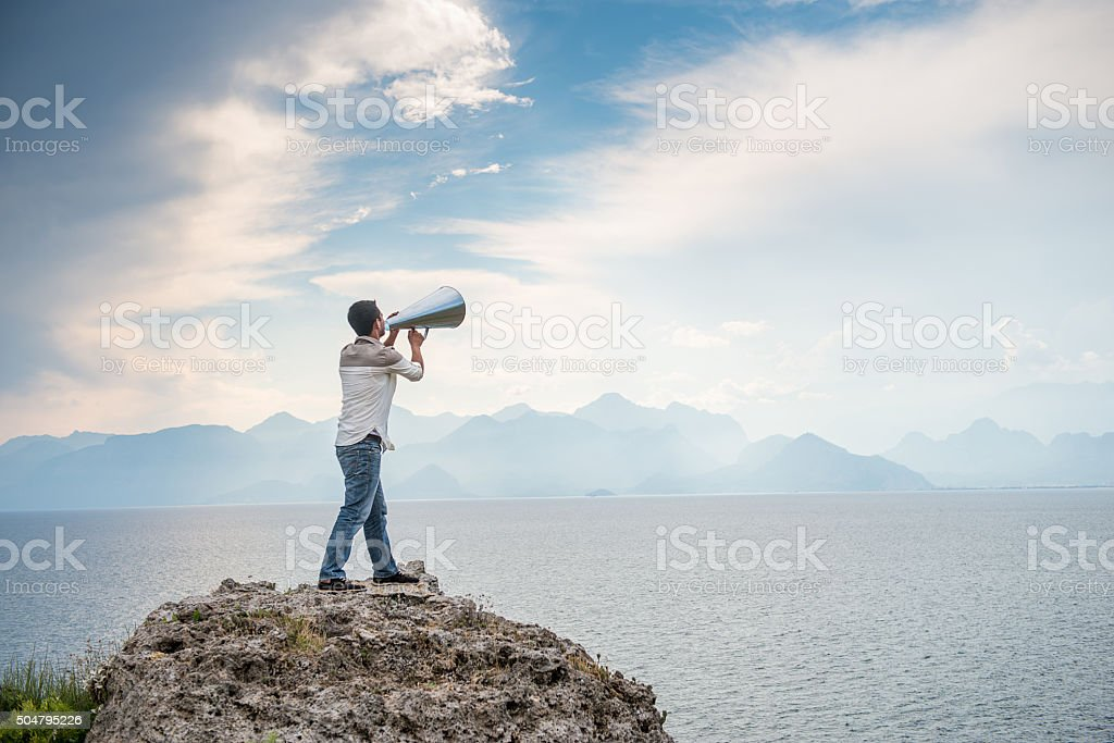 Young man shouting into megaphone stock photo