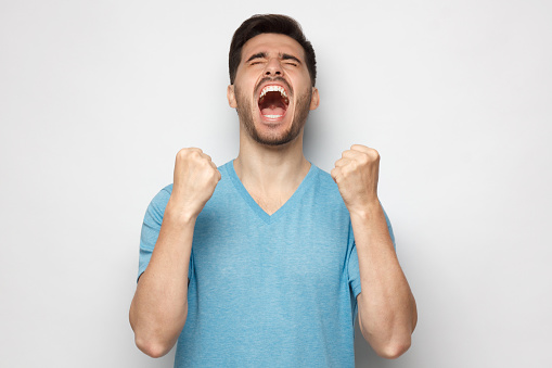 Young man shouting with closed eyes, celebrating victory, squeezing fists in deep emotional expression of happiness and luck, isolated on gray background