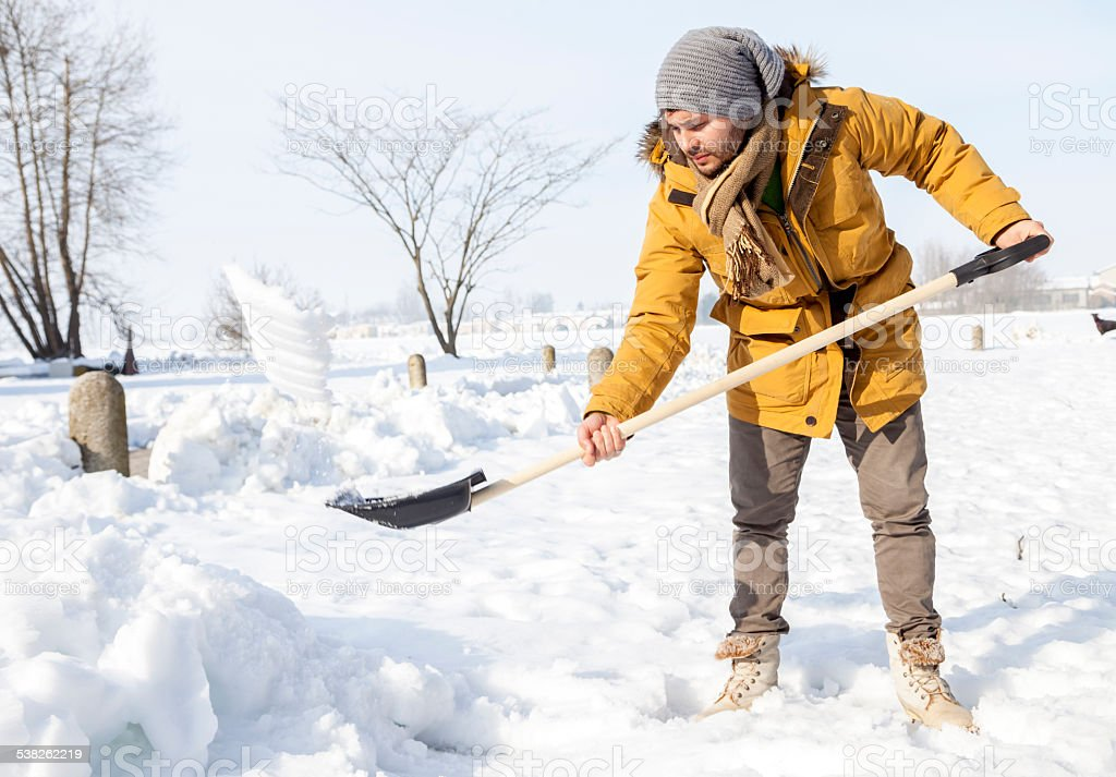 young man shoveling snow in the country stock photo