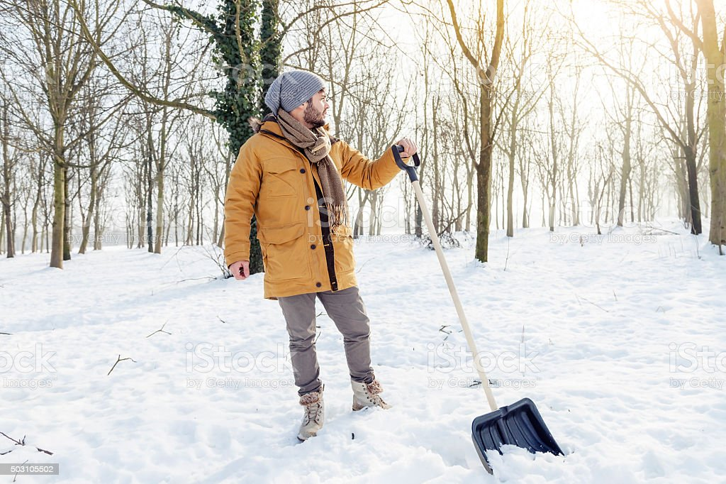 young man shoveling snow near a small wood stock photo