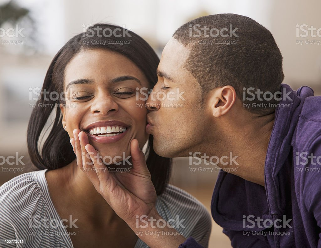 Young man showing affection with young woman stock photo