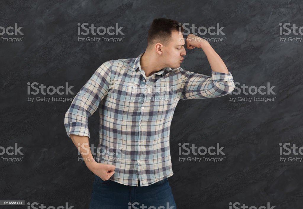 Young man showing and kissing his biceps royalty-free stock photo