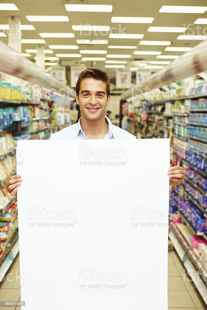 Young man showing blank board at super market royalty-free stock photo