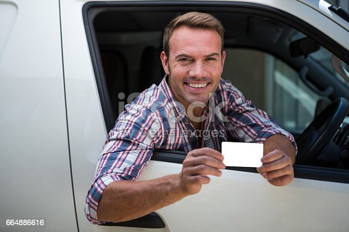 1051147634 istock photo Young man showing his drivers license 664886616