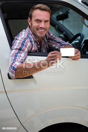 1051147634 istock photo Young man showing his drivers license 664886658