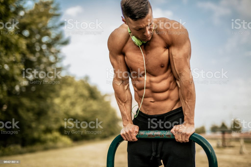 Young man showing his muscles in the local park - Royalty-free Abdominal Muscle Stock Photo