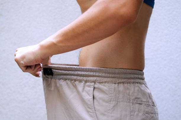 Young man showing how much he got his weight lost by pulling his pants.Guy checking size his genital Man after diet comparing his waist size of trousers.Slim fit male body or genital issue. reproductive organ stock pictures, royalty-free photos & images