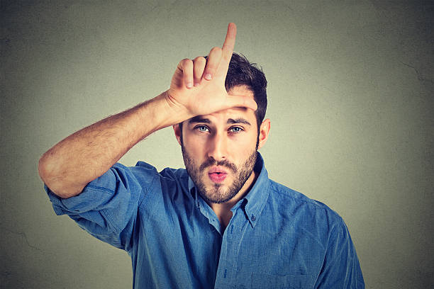 young man showing loser sign looking at you with disgust Closeup portrait of serious young man showing loser sign on forehead, looking at you with disgust at camera gesture isolated on gray background. Negative human emotions, facial expressions, feelings antagonize stock pictures, royalty-free photos & images