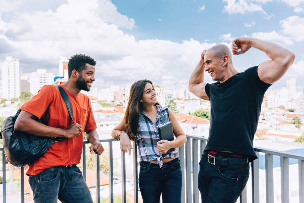 Young man showing off his muscles to his friends stock photo