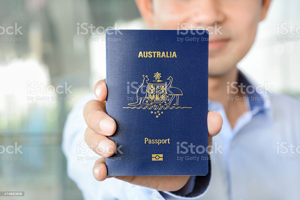 Young man showing passport (of Australia) stock photo