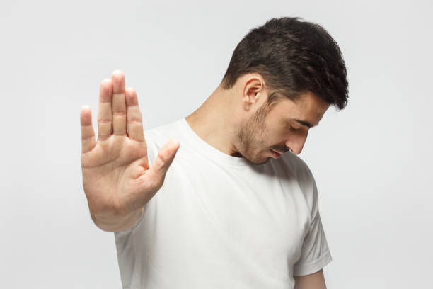 young man showing stop gesture, isolated on background - going inside eye imagens e fotografias de stock