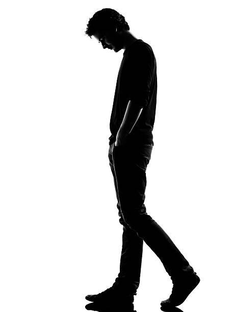 silhouette giovane uomo triste a - guardare verso il basso foto e immagini stock