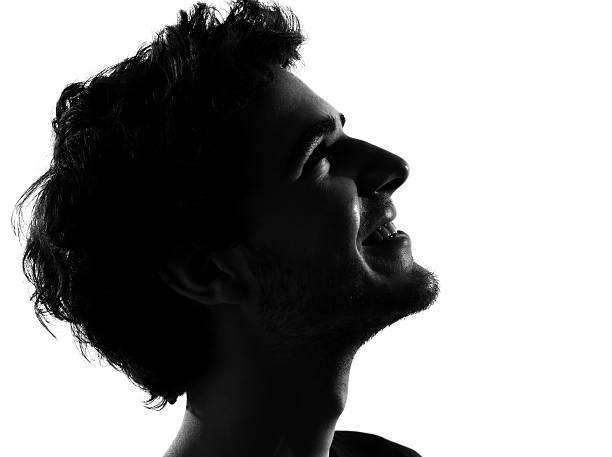 junger mann silhouette glücklich similing - gegenlicht stock-fotos und bilder