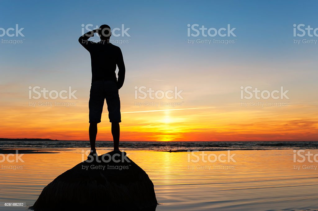 Young man silhouette standing on the rock at sunset background stock photo