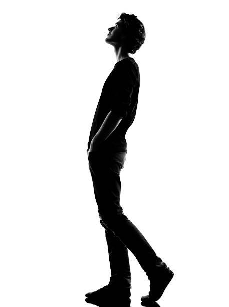 young man silhouette walking looking up - arkadan aydınlatmalı stok fotoğraflar ve resimler