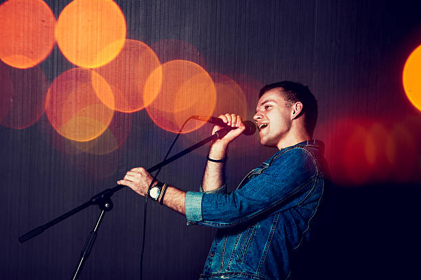 Young Man Singing with Microphone. Young Man Singing with Microphone. Singer Performance. Concert and Music Concept. Toned Photo with Bokeh. singer stock pictures, royalty-free photos & images