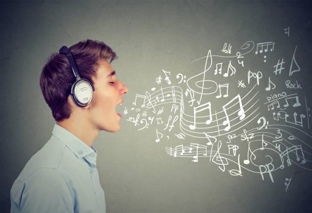 junger mann singen mit noten aus mund kommt - one song training stock-fotos und bilder
