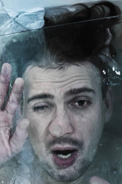 a young man sinking in the water - brüllender tod stock-fotos und bilder
