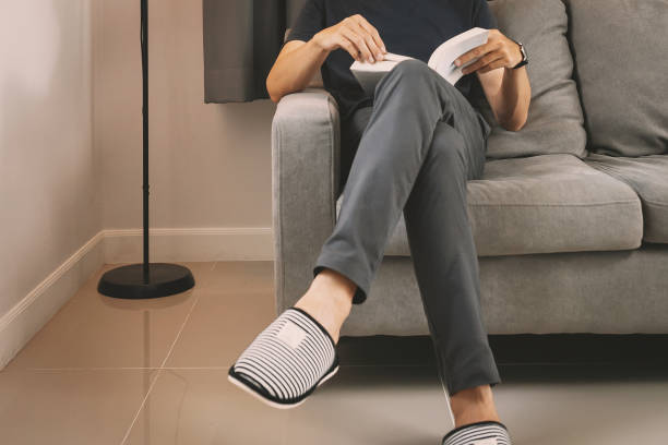 Young man sit down on the sofa reading book at home stock photo