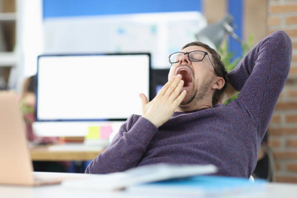 Young man siting at table in office and yawning stock photo