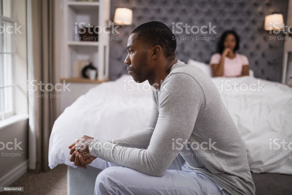 Young man siting while woman resting on bed at home stock photo