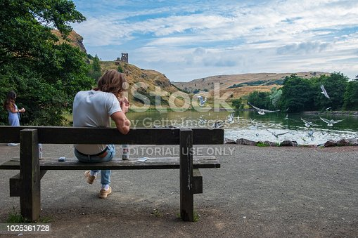 Edinburgh, United Kingdom - July 27, 2018: Young man sits and smokes on a bench by St Margaret