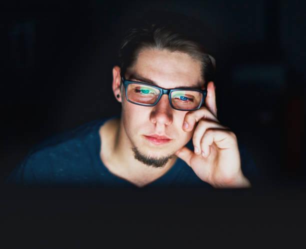 Jeune homme se trouve dans l'écran d'ordinateur à regarder sombre - Photo