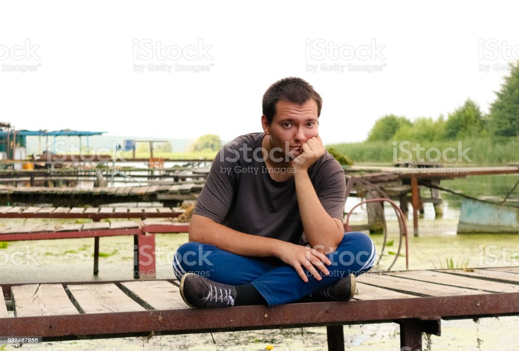 A young man sits on a bridge, on a river on a warm summer day.  Rest on the open air. stock photo
