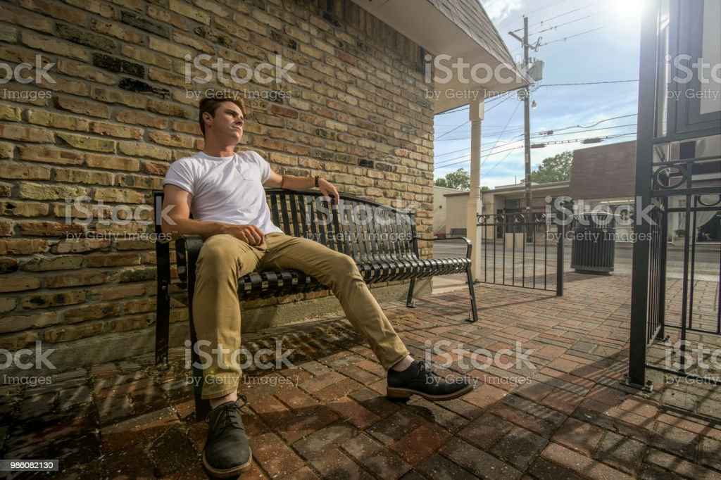 Young man sits on outside bench. stock photo