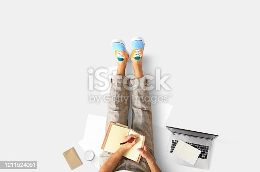 1175668510 istock photo A young man sits on the floor and writes 1211524051