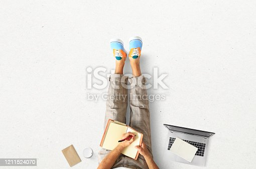 1175668510 istock photo A young man sits on the floor and writes 1211524070