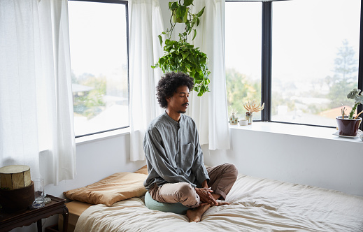Young African American man sitting on his bed with his eyes closed and legs crossed during a meditation session