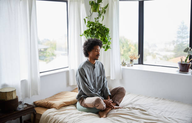 Young man sitting alone on his bed and meditating stock photo