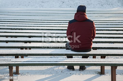 Young man sitting alone on wooden bench in sunny winter day. Snow covered bleachers. Thinking about life. Back view.