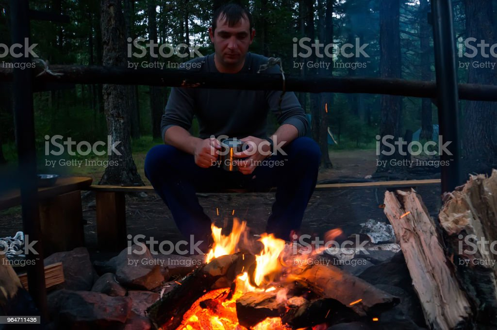 Young man sitting and drinking tea while looking at fire royalty-free stock photo