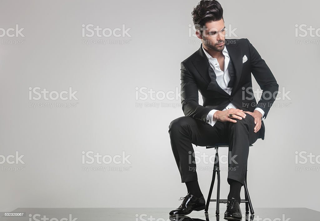 young man sitting and holding one hand on his knee. stock photo