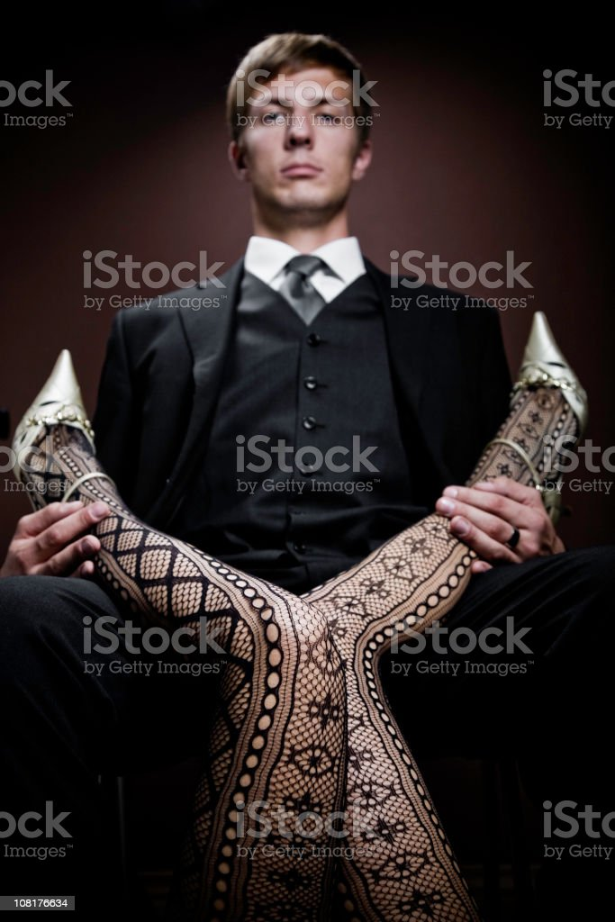 Young Man Sitting and Holding Woman's Legs royalty-free stock photo