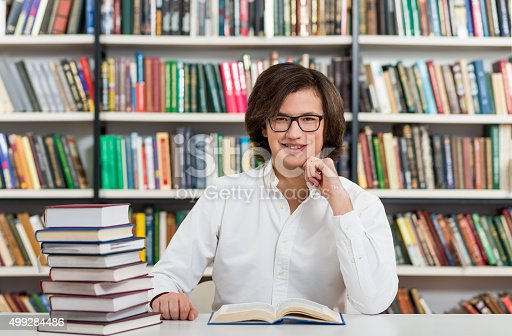 500129038istockphoto young man sitting at a desk in the library 499284486