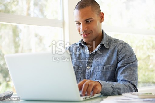 istock Young man sitting at a table using a laptop 155075074