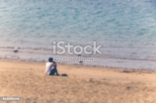 istock Young man sitting at beach alone. 845589444
