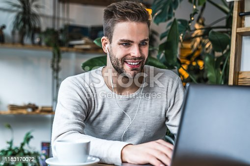 istock Young man sitting at cafe table using laptop in earphones 1183170072