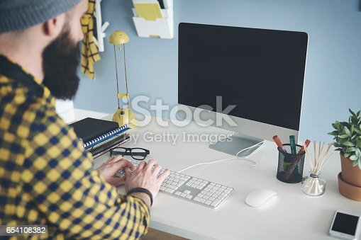 istock Young man sitting at desk working on computer 654108382