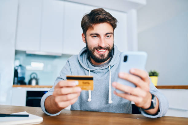 Young man sitting at home paying for food online with smartphone and credit card stock photo