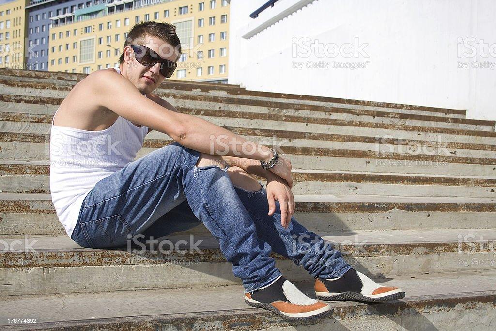 Young man sitting at steps royalty-free stock photo