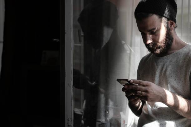 joven sentado en la ventana con el teléfono inteligente - social media fotografías e imágenes de stock