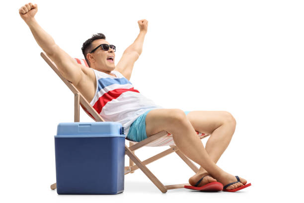 Young man sitting in a deck chair gesturing happiness stock photo