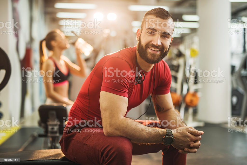 Young man sitting in a gym and looking at camera. royalty-free stock photo