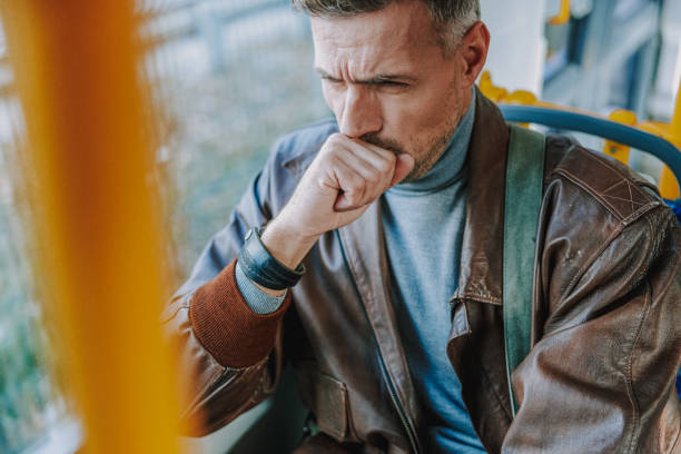 Young man sitting in a tram and coughing stock photo